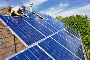 Man installing alternative energy photovoltaic solar panels on roof